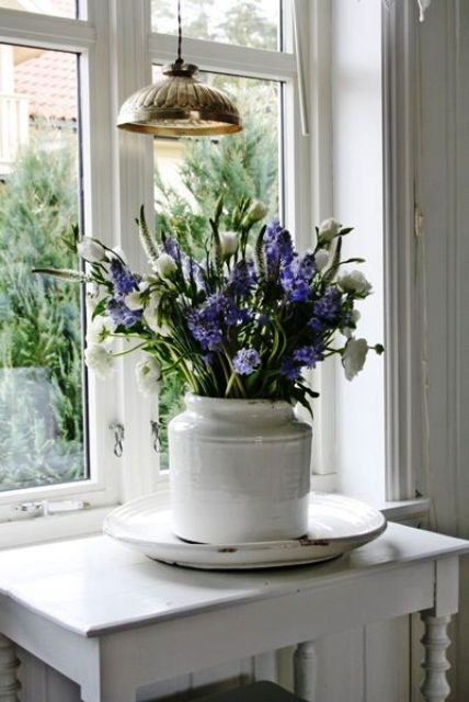 a white vase with white ranunculus and purple hyacinths is a lovely idea for a vintage rustic or Scandi space