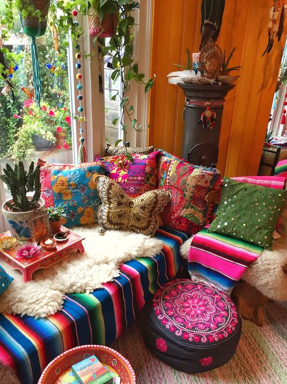 an extra colorful boho sunroom with a bright sectional, colorful pillows, blakets, ottomans, potted plants and pompoms