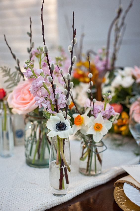 bottles and vases with willow, white blooms, pink and lilac blooms look fresh and spring-like