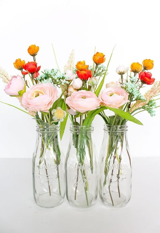 bottles with pink ranunculus and smaller red and orcher blooms plus grasses are fresh spring decorations
