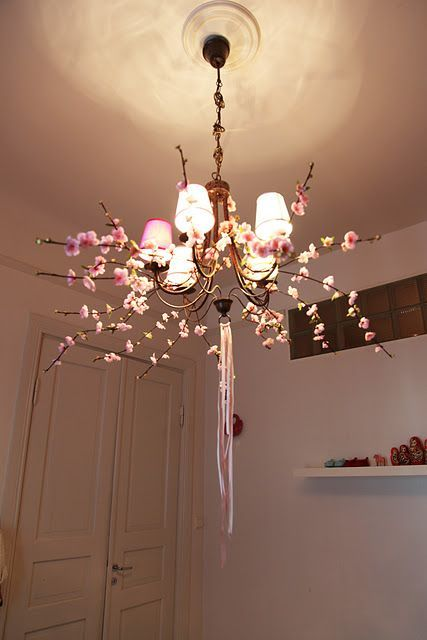 decorate your chandelier with silk blooming branches and ribbons to make it feel like spring