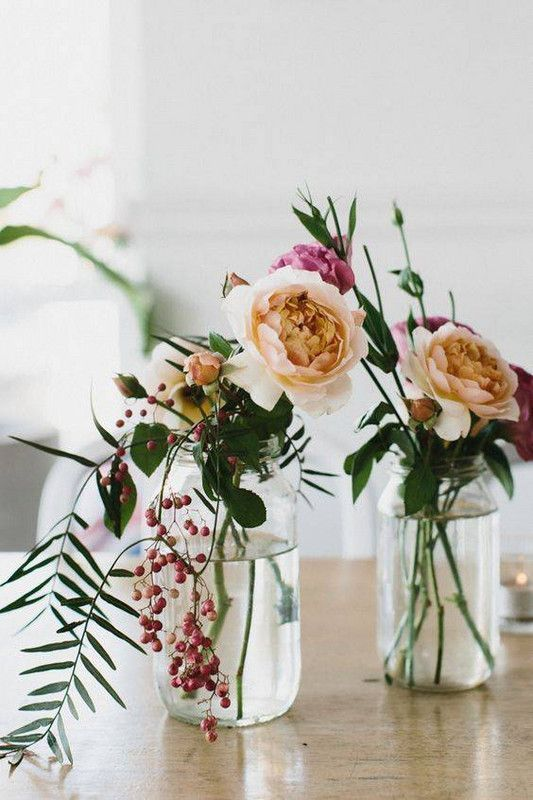 very simple floral arrangements in jars - berries, peachy and pink blooms, some foliage for a modern and relaxed space