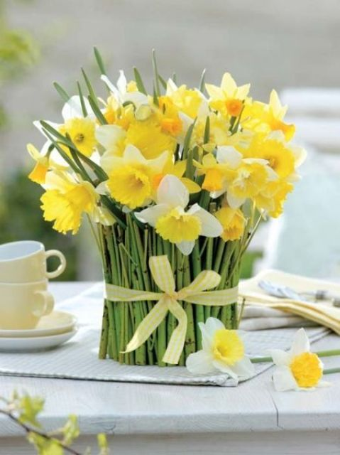 white and yellow daffodils wrapped with green stems and with a yellow ribbon is a pretty spring decor idea