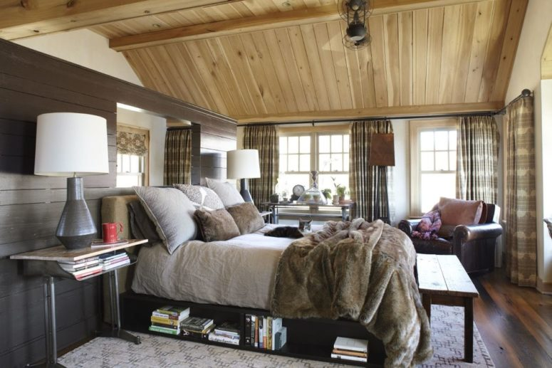 a cozy farmhouse bedroom with much wood, printed curtains and a bed with storage space (Dan Ruhland Designs LLC)