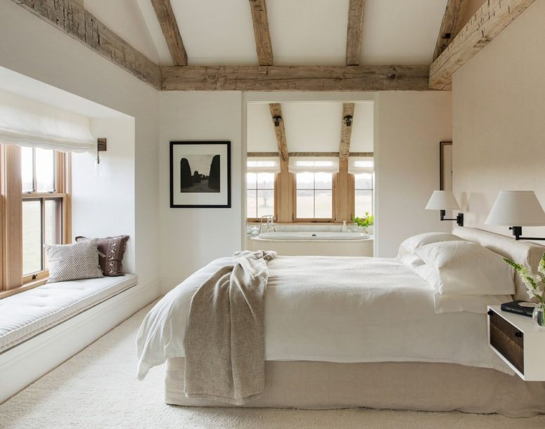 a contemporary farmhouse bedroom with weathered wood ceiling beams, neutral textiles and much natural light  (Finstad's Carpet One)