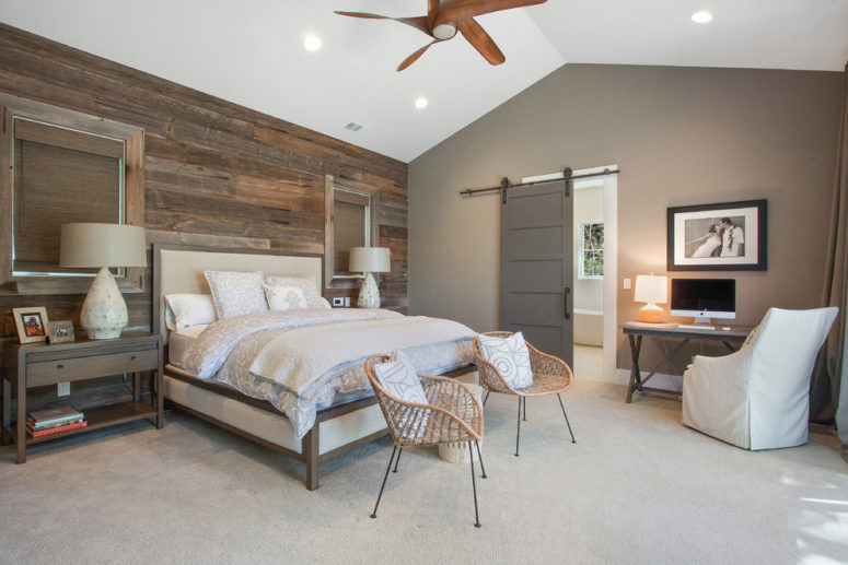 a contemporary meets farmhouse bedroom with a weathered wooden wall, rattan chairs, a sliding barn door  (LMK Interiors)