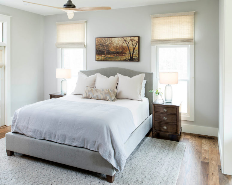 a neutral farmhouse bedroom done in powder blue and grey, with wooden furniture and much natural lights  (Chelsea Benay, LLC)
