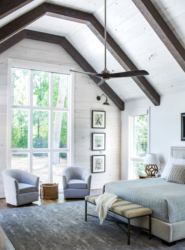 a large airy farmhouse bedroom done with white walls, dark stained ceiling beams and comfy furniture  (Sheehan Built Homes)