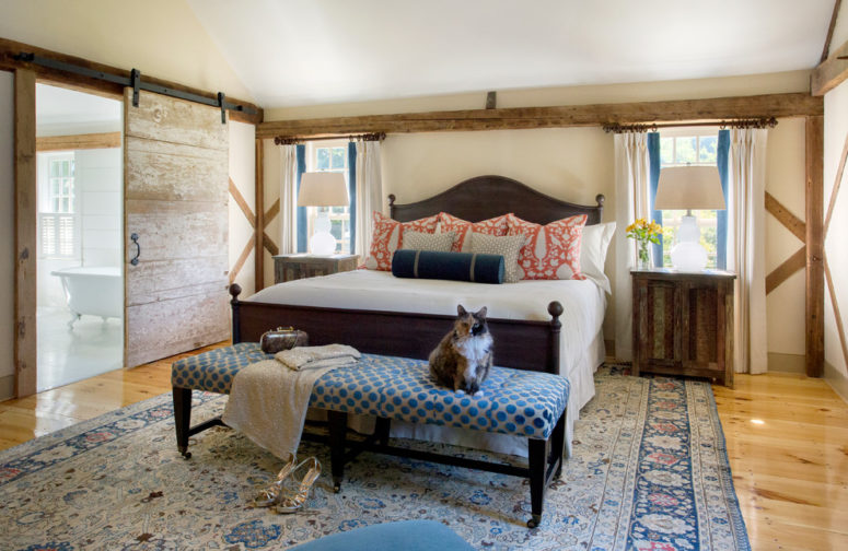 a farmhouse bedroom with much weathered and aged wood, traditional textiles and a sliding barn door  (Cummings Architects)