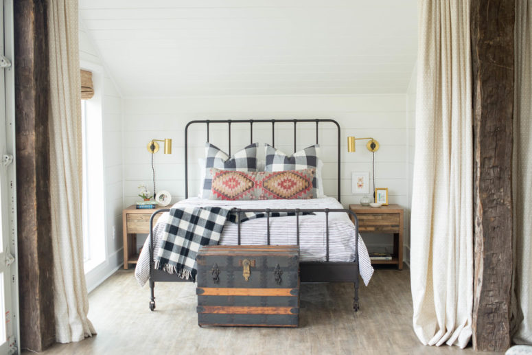 a neutral farmhouse bedroom with wooden nightstands, a forged bed and a chest for storage   (Sarah Catherine Design)
