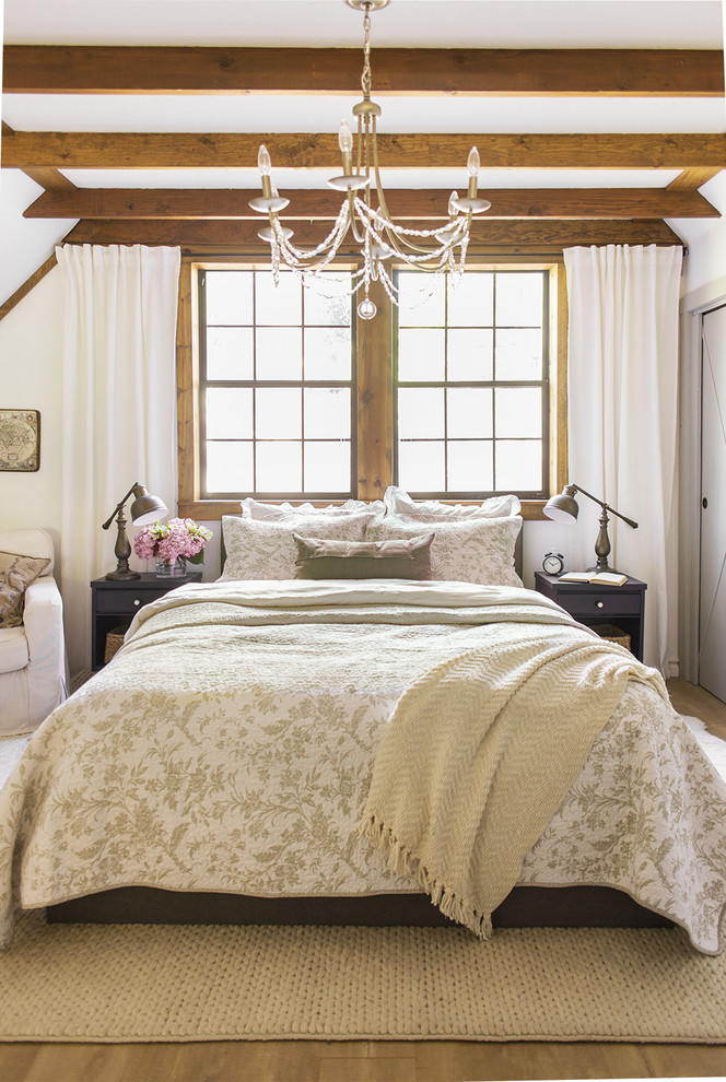 a vintage meets farmhouse bedroom with wooden beams on the ceiling, light-colored walls and some printed textiles  (Jenna Sue Design Co.)