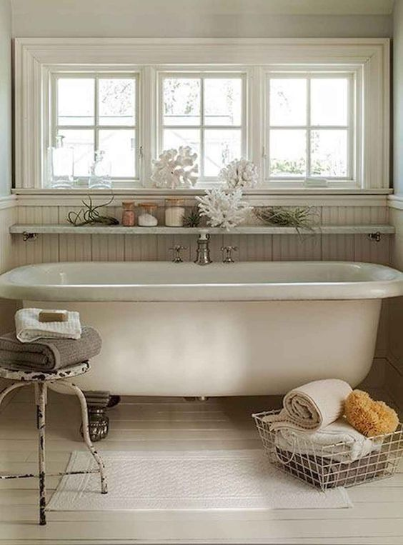 a beach bathroom with beadboard, a vintage clawfoot tub, a wire basket and a metal stool
