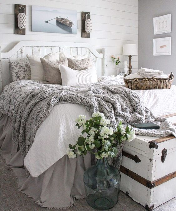 a beach farmhouse bedroom in neutrals with a whitewashed bed and walls plus a chest and cozy textiles