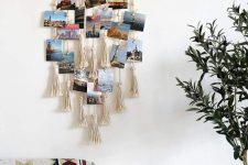 a boho wall hanging with tassels and photos hanging on ropes and macrame on it is very cool to DIY