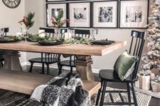 a bright and contrasting dining area with a wooden dining set, black chairs, a black frame and bulb chandelier and a gallery wall
