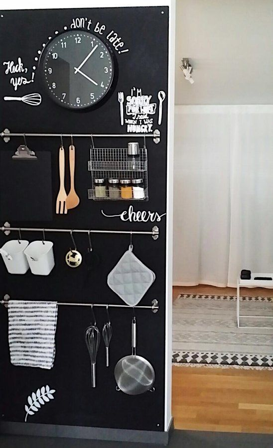 a chalkboard wall with railings, holders, hooks, a clock and lots of notes here and there is ideal for a kitchen