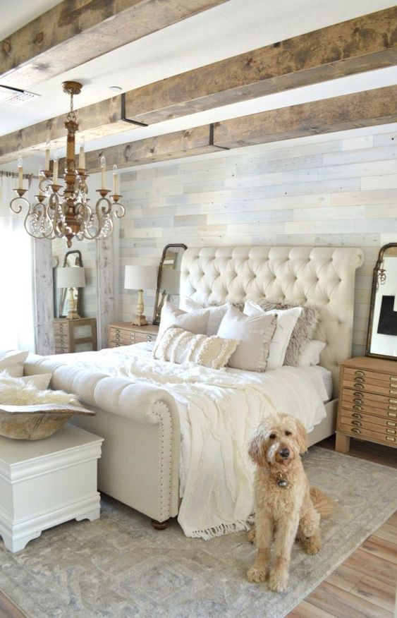 a chic famrhouse bedroom with wooden beams, elegant furniture and a crystal chandelier