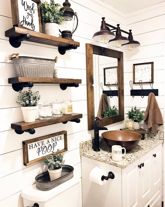 a chic farmhouse bathroom with white plank walls, stained wooden shelves, a white vanity and a metal sink