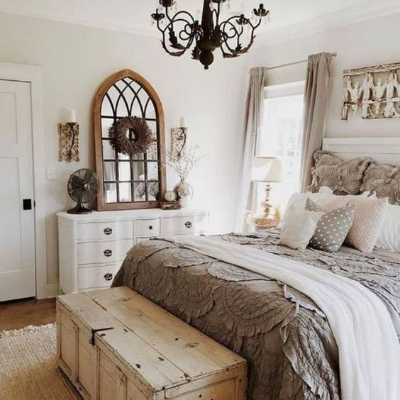 a chic farmhouse bedroom in neutrals, with vintage furniture, a chest for storage and a metal chandelier