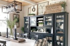 a chic farmhouse dining area with a black and glass buffet, signs, a white table and checked chairs and a frame chandelier