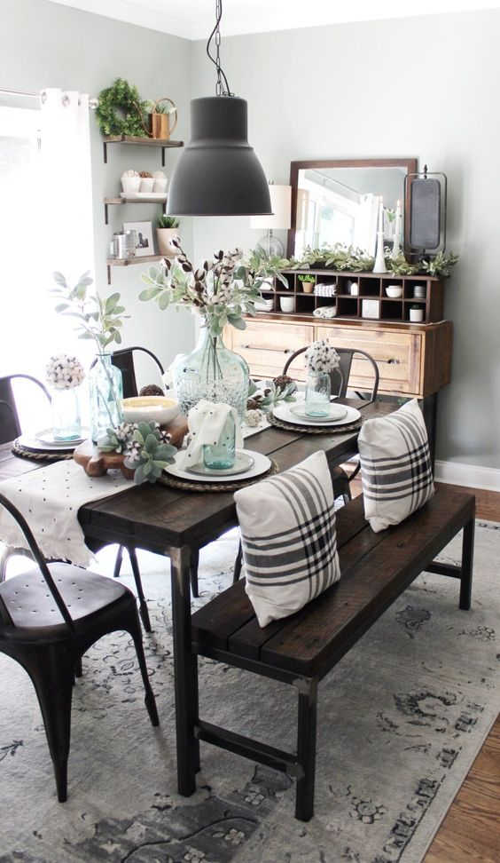 a chic farmhouse dining space with a wooden buffet, a dark stained wooden dining set, a metal lamp and lots of greenery