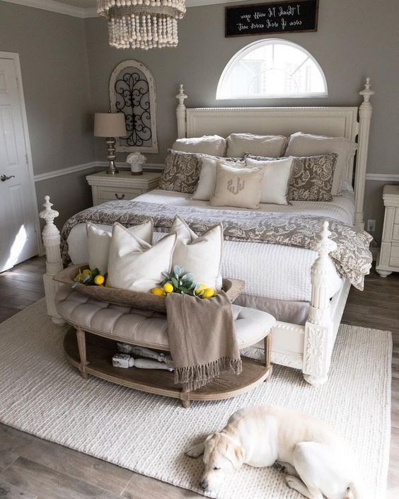 a chic taupe and creamy farmhouse bedroom with elegant furniture, a bead chandelier and an uphostered ottoman