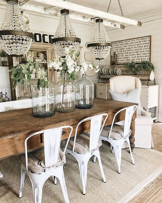 a chic vintage farmhouse dining area with crystal chandeliers, a sign, a shabby chic buffet, a wooden table and metal chairs