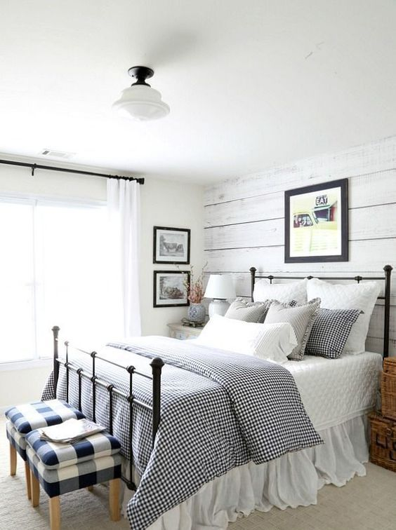 a classic farmhouse bedroom with whitewashed wooden walls, checked and gingham prints and a metal bed