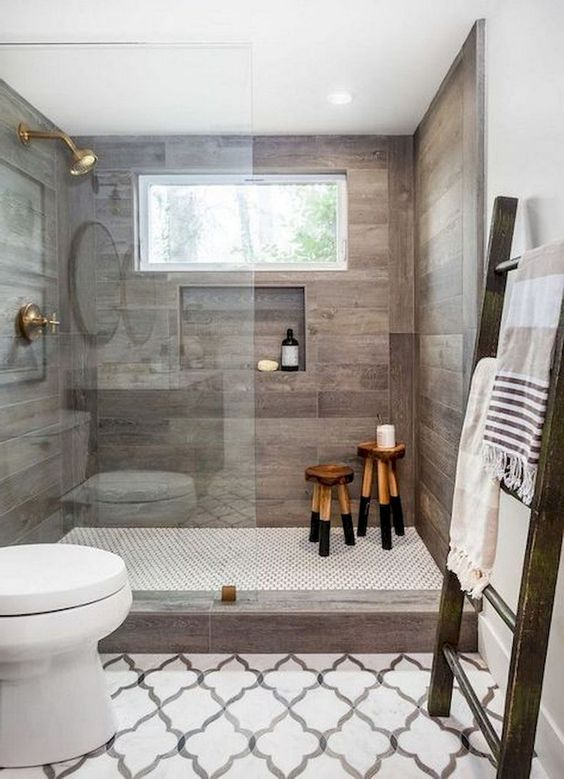 a contemporary farmhouse bathroom with mosaic tiles on the floor, wood-inspired tiles in the shower and a large ladder