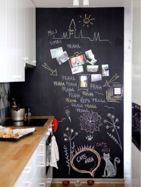 a contemporary white kitchen with a chalkboard wall that is pure art, your kids will love it