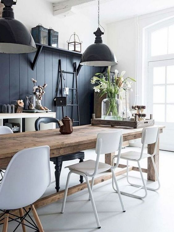 a contrasting monochromatic dining area with a black wall, a wooden table, white chairs, black pendant lamps