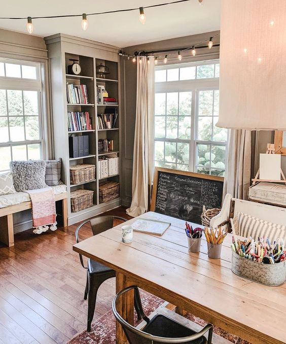 a cottage home office with a wooden desk, a chalkboard sign, a built in storage unit and a bench is very welcoming and cool