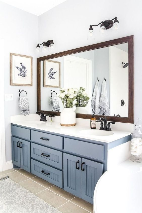 a cozy farmhouse bathroom with a serenity blue vanity, a tub, a large mirror and black fixtures for a more dramatic look