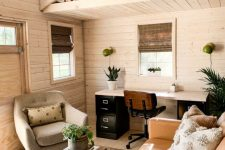a cozy farmhouse home office with a leather sofa, a cool chair, a contrasting desk and everything around clad with wood