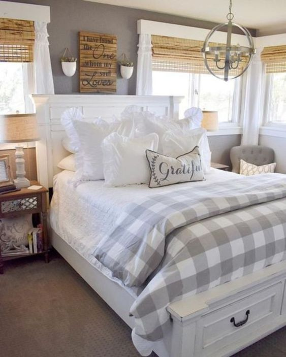 a cozy farmhouse space with wooden shades, checked textiles, a rustic artwork and carpet flooring