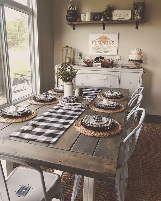 a cozy traditional farmhouse dining room with checked textiles, a wooden table, metal chairs and a buffet