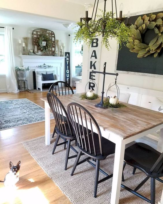 a cute farmhouse dining nook with a chalkboard, a greenery wreath, a wooden dining table, black chairs and a chandelier