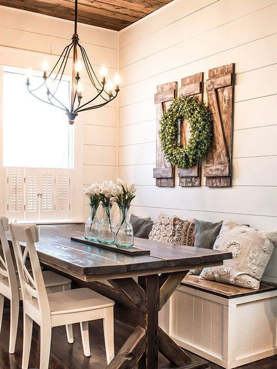 a cute neutral farmhouse dining nook with a built-in bench, a wooden table, white chairs and a metal chandelier