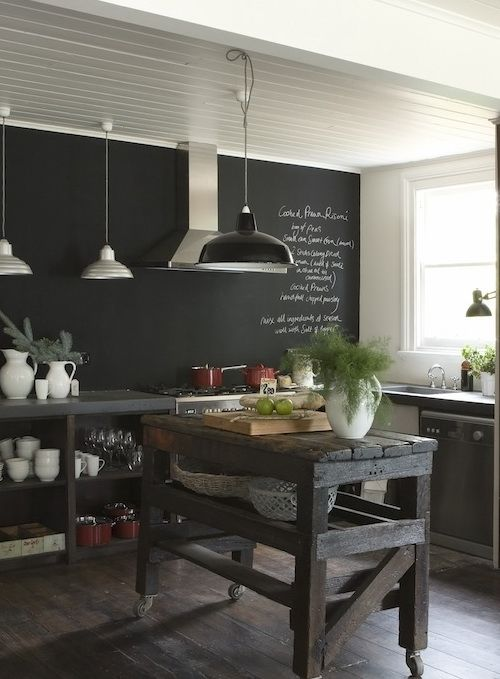a dark kitchen with a chalkboard wall, wooden kitchen island, concrete and stone cabinets and pendant lamps