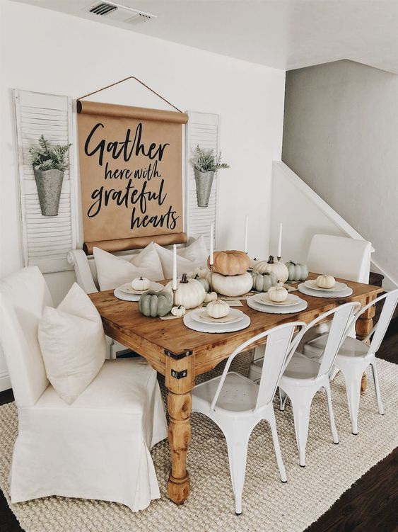 a fall modern farmhouse dining room with a sign, metal planters, a wooden table, metal and upholstered chairs