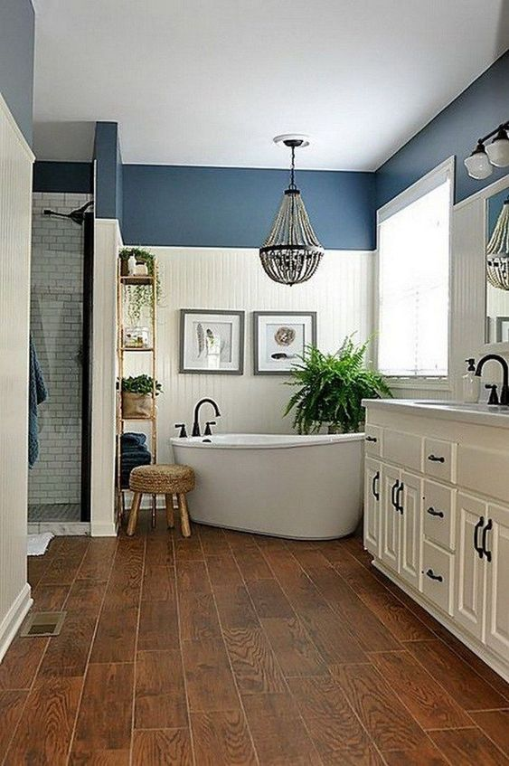a farmhouse bathroom done in white and blue, with rich-stained wood, a bead chandelier and a vintage white vanity
