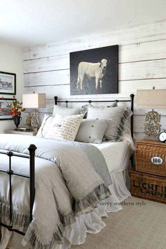 a farmhouse bedroom with whitewashed walls, neutral textiles, basket boxes and a cow artwork