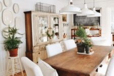 a farmhouse dining area with stained furniture, white covered chairs, potted greenery and white pendant lamps