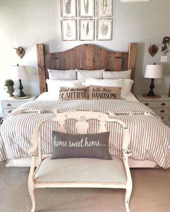 a farmhouse space with a gallery wall, a wooden bed, a vintage bench and striped bedding