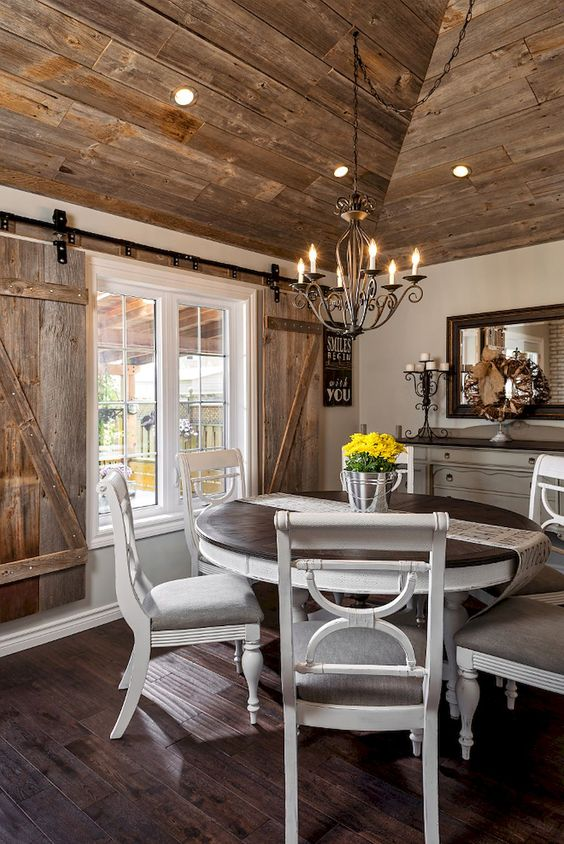 a farmhouse wooden dining area with shutters, vintage white furniture and a framed mirror
