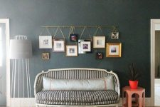 a gold photo rail with color family photos in mismatching frames hanging on it is a cool photo display idea