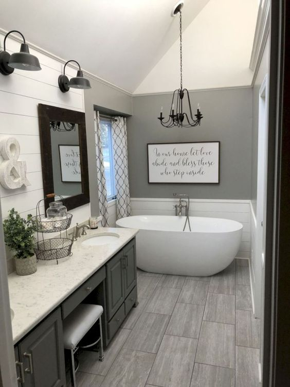 a grey farmhouse bathroom with a large vintage vanity, a stone countertop, an oval tub, a chandelier and some vintage wall lamps