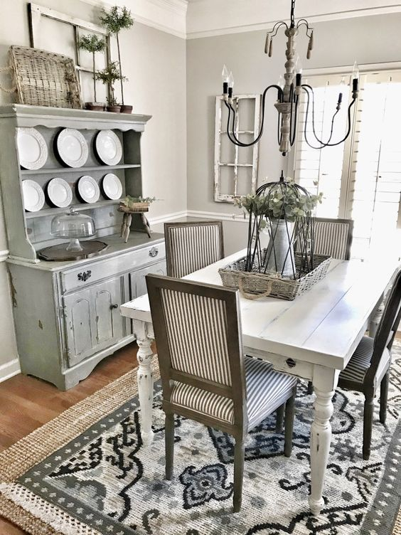a greyish living room with a whitewashed buffet, a white table, striped chairs and a vintage chandelier