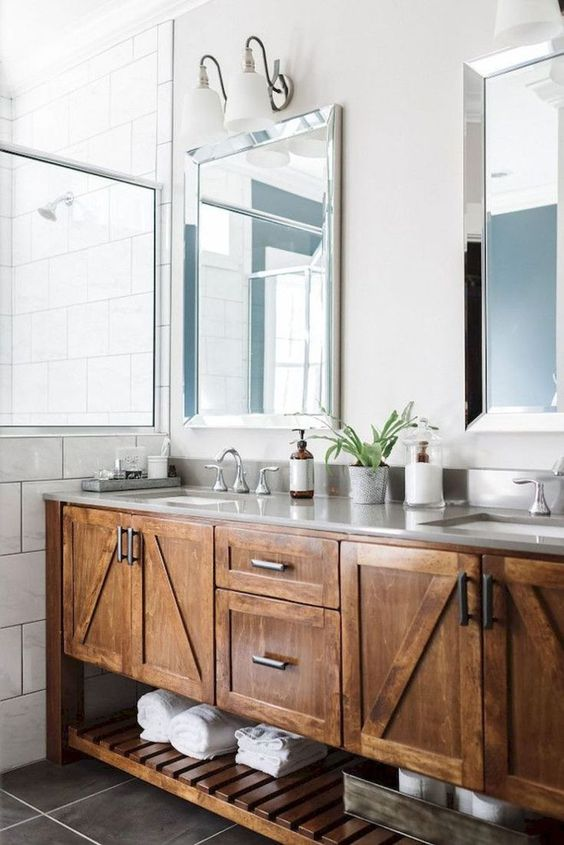 a large farmhouse bathroom with a large stained wooden vanity, mirrors and potted plants