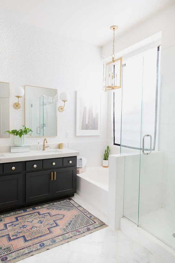 a light-filled farmhouse bathroom with a black vanity, gilded touches, white tiles and lamps